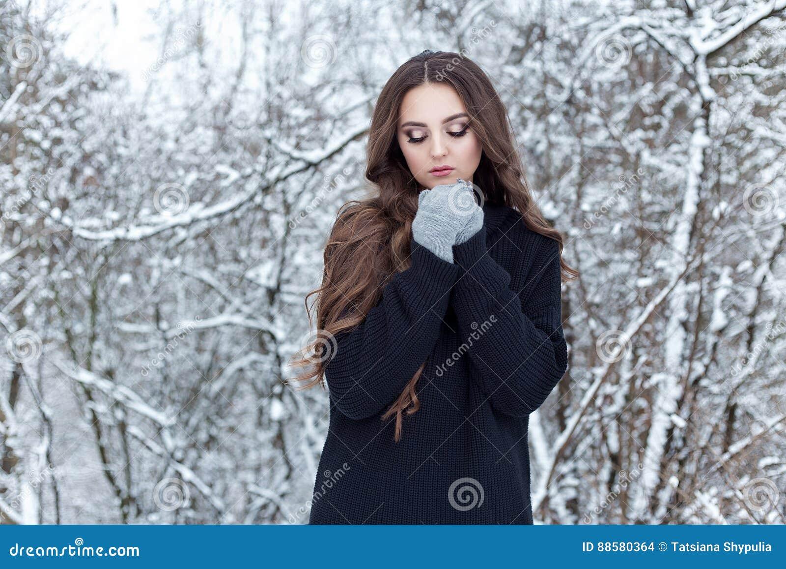 Den härliga unga kvinnan med långt ledset ensamt för mörkt hår går i vinterträna i ett svart omslag och tumvanten