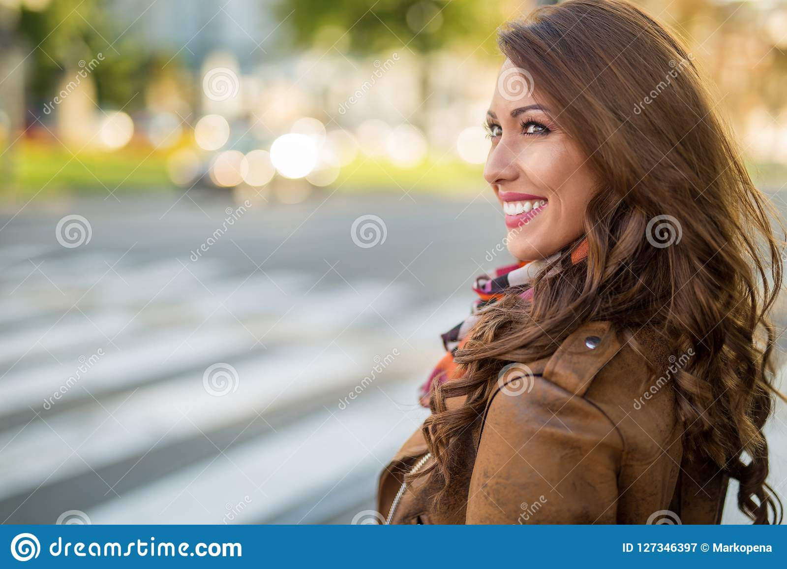 Den härliga unga kvinnan som ler, medan vänta på ett kors, går