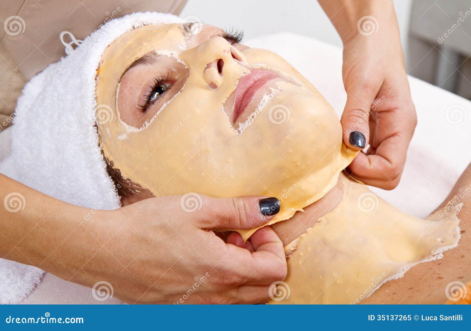 Den härliga unga kvinnan tar bort den ansikts- maskeringen i en skönhetmitt