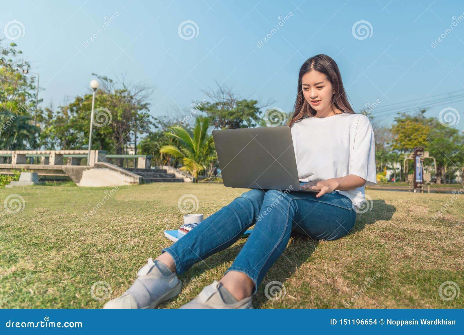 Den härliga unga le kvinnan som använder minnestavlan parkerar offentligt