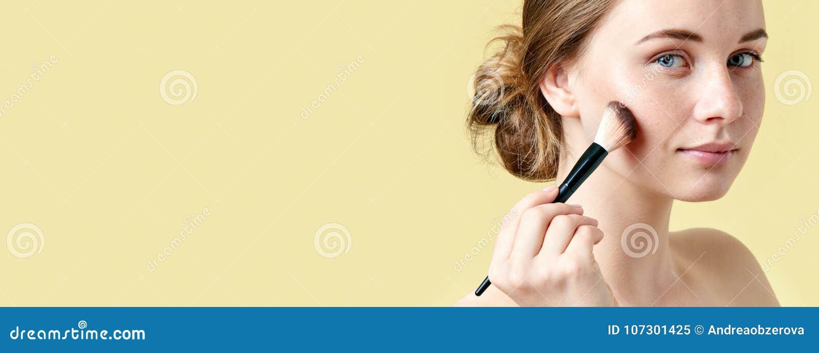 Den härliga unga rödhårig mankvinnan med fräknar som drar upp konturerna av hennes kindknotor som använder smink, borstar skönhet