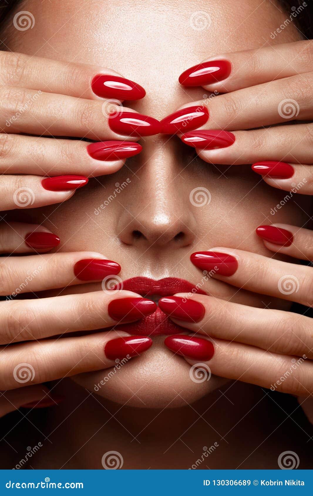 Den härligt flickan med ett klassiskt smink och rött spikar Manikyrdesign Härlig le flicka