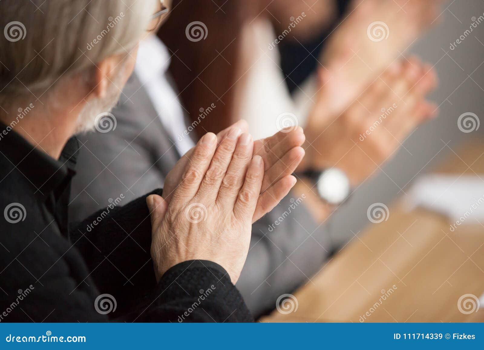 Den höga gråhåriga affärsmannen som applåderar händer som deltar i, conferen