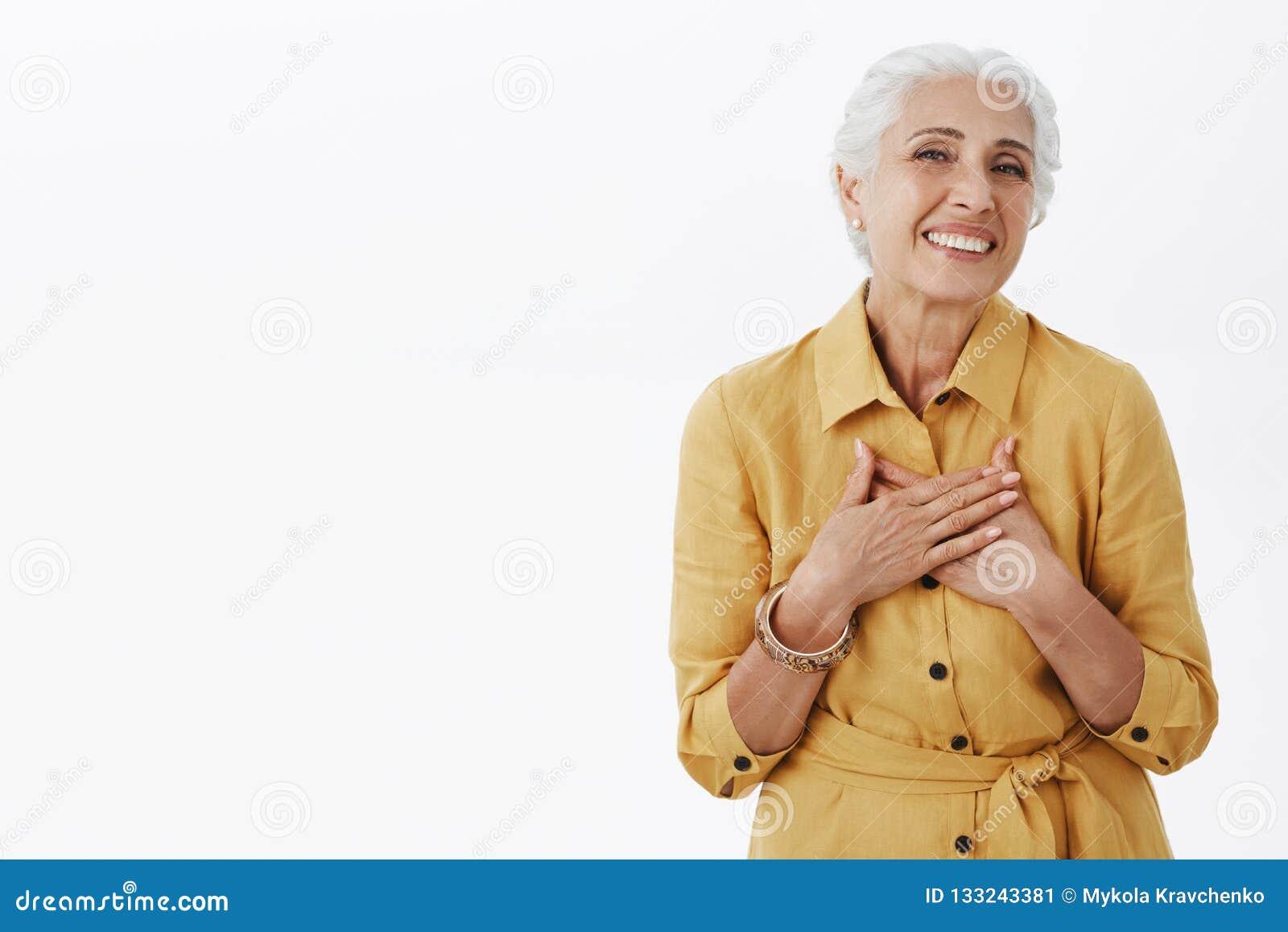 Den höga kvinnan håller att få komplimang som ser nya och härliga Förtjust lycklig charmig gammal dam med vitt hår in