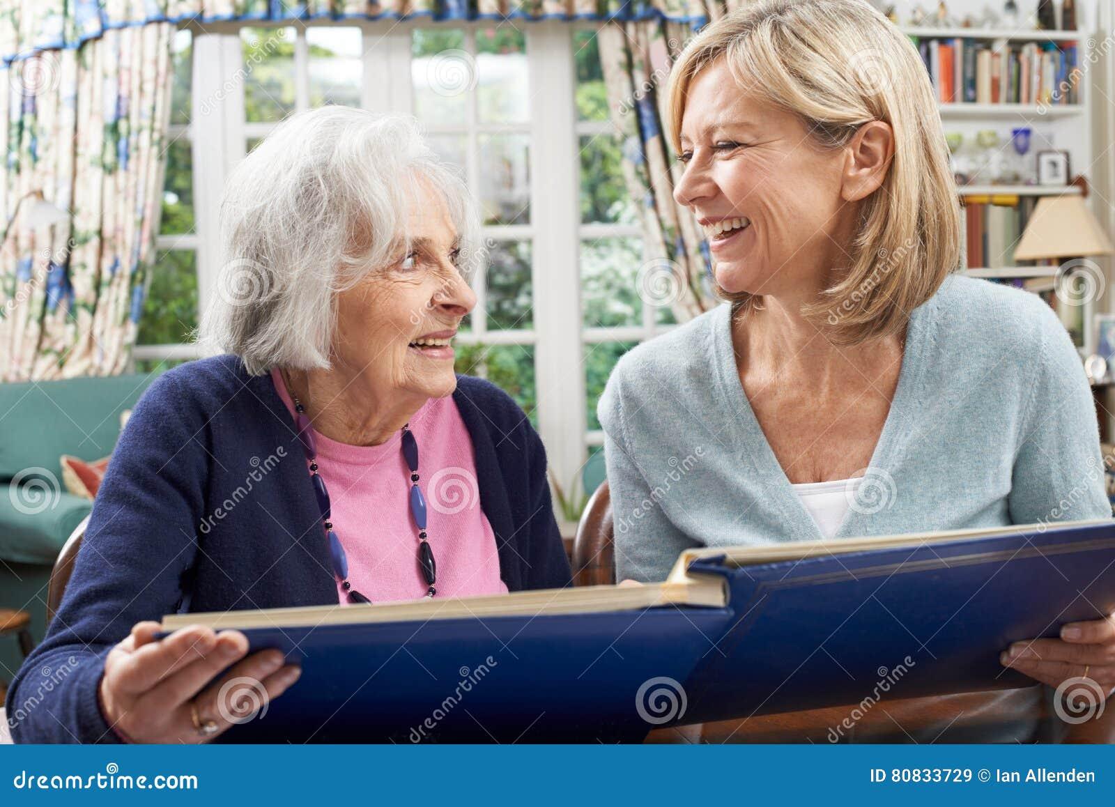 Den höga kvinnan ser fotoalbumet med den mogna kvinnliga grannen