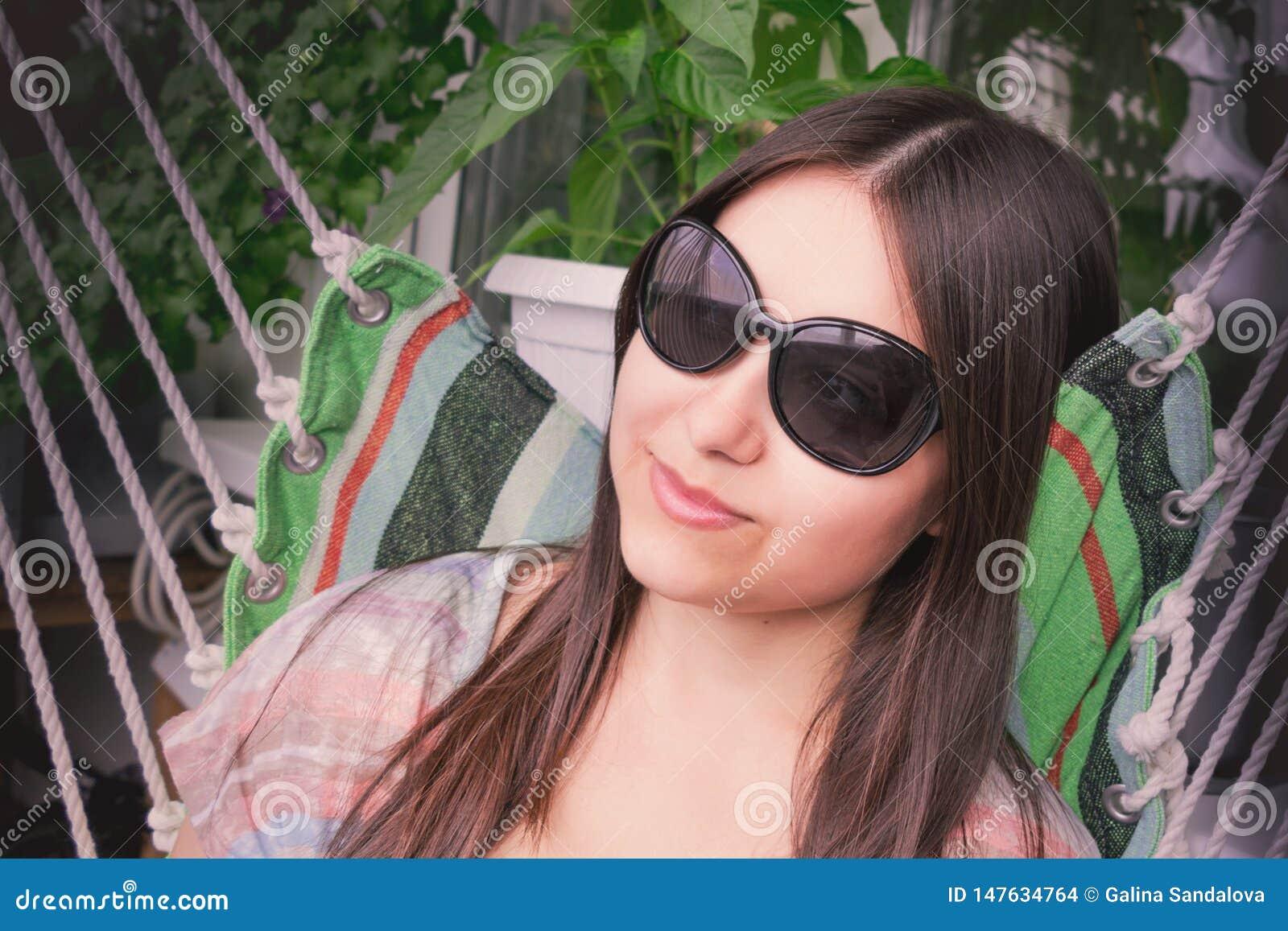 Den h?rliga flickan med l?ngt m?rkt h?r i solglas?gon vilar sammantr?de i en h?ngmatta p? balkongen