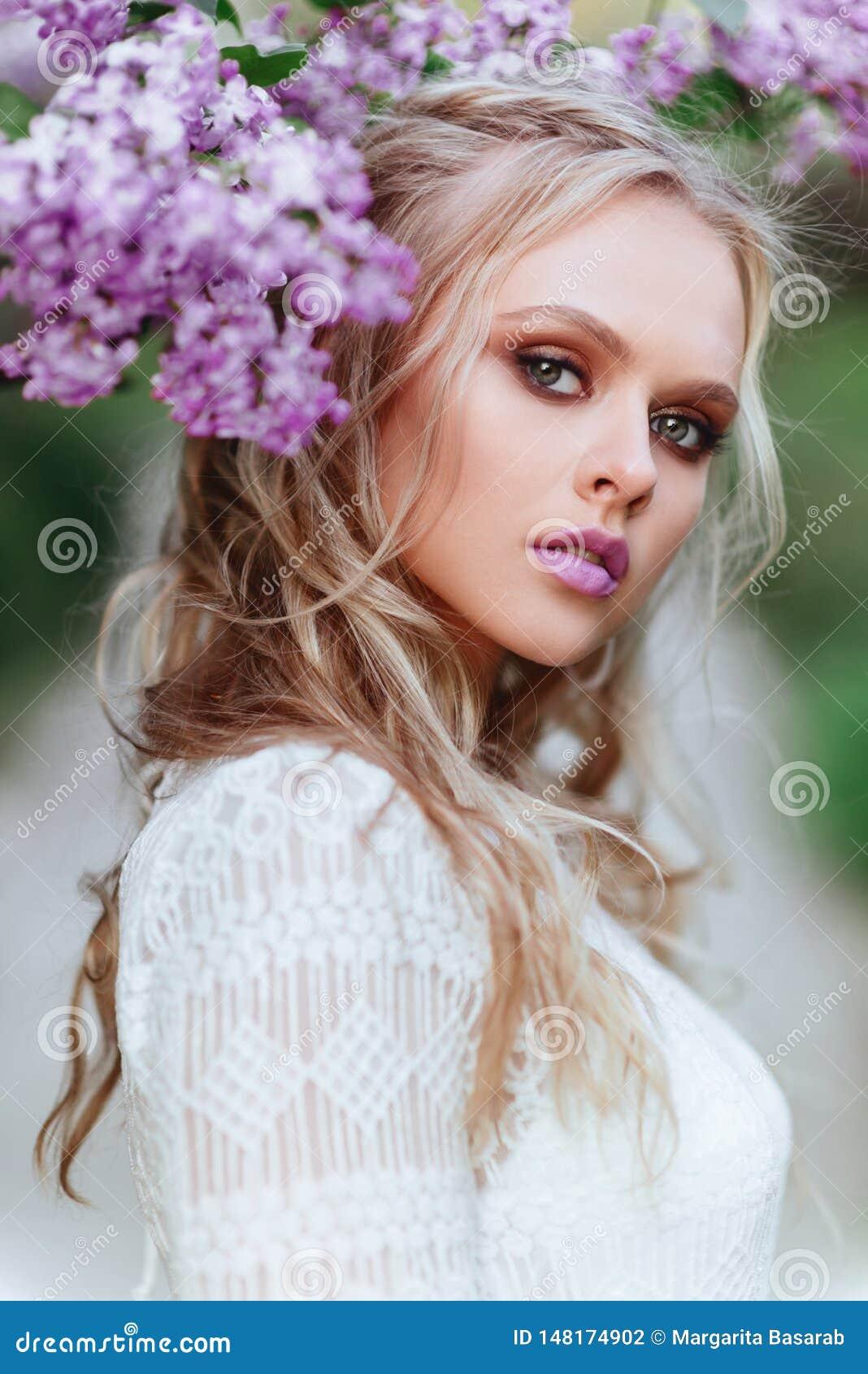 Den h?rliga kvinnan som tycker om lilatr?dg?rden, den unga kvinnan med blommor i gr?splan, parkerar