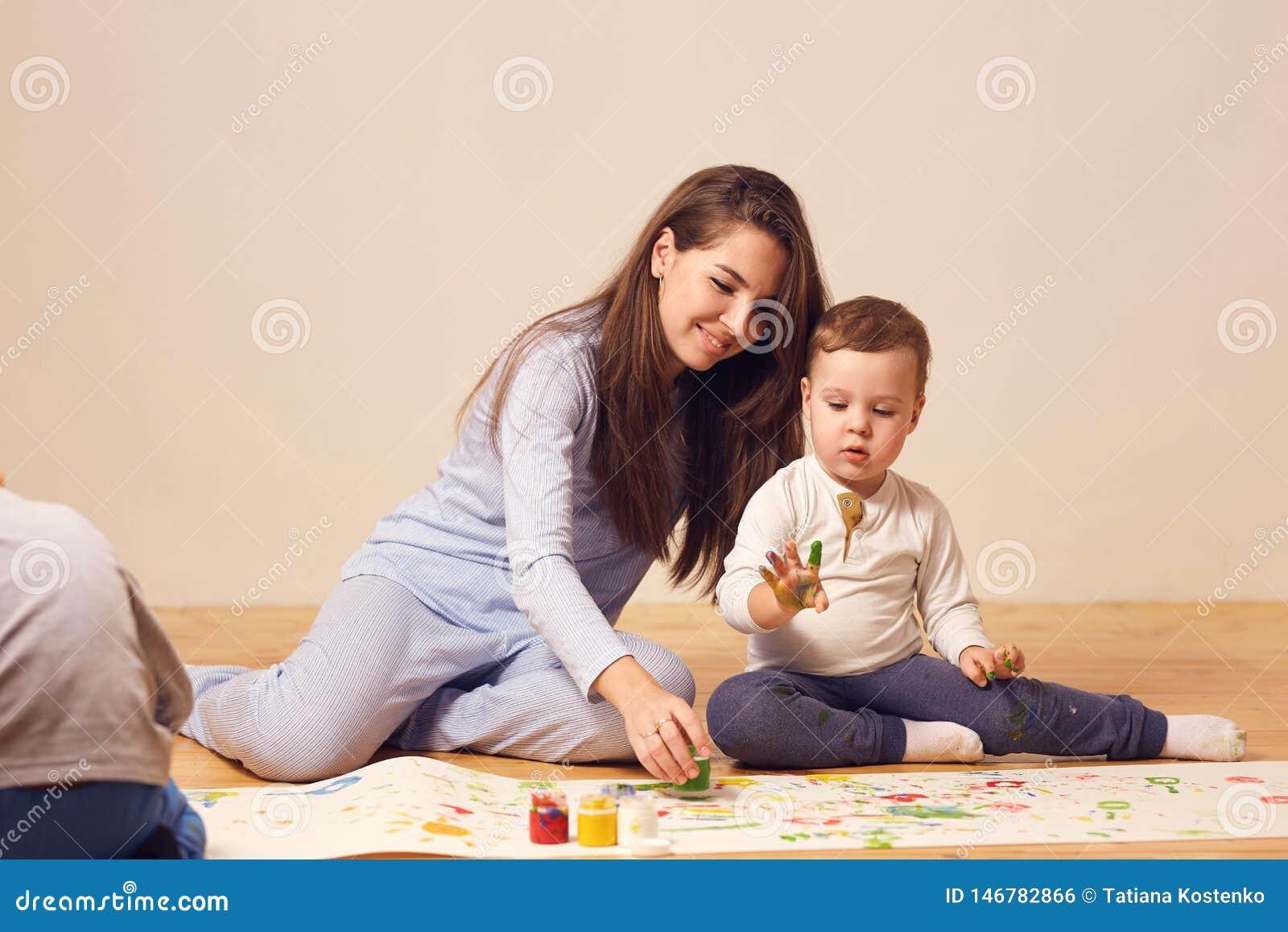 Den h?rliga lyckliga unga modern och hennes ikl?dda hem- kl?der f?r liten son sitter p? tr?golvet i rummet och
