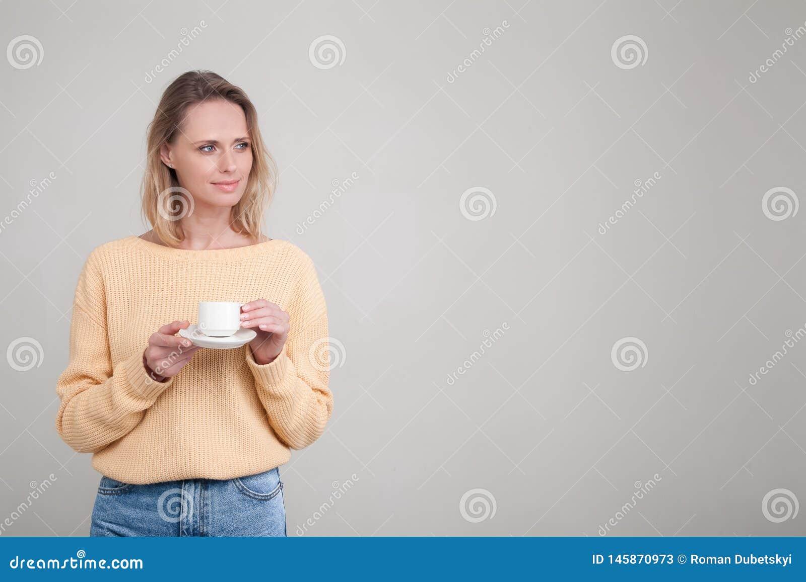 Den h?rliga unga mjuka flickan med blont h?r som st?r med en kopp kaffe i hennes h?nder, ?r hon ikl?dd en gul tr?ja poserar