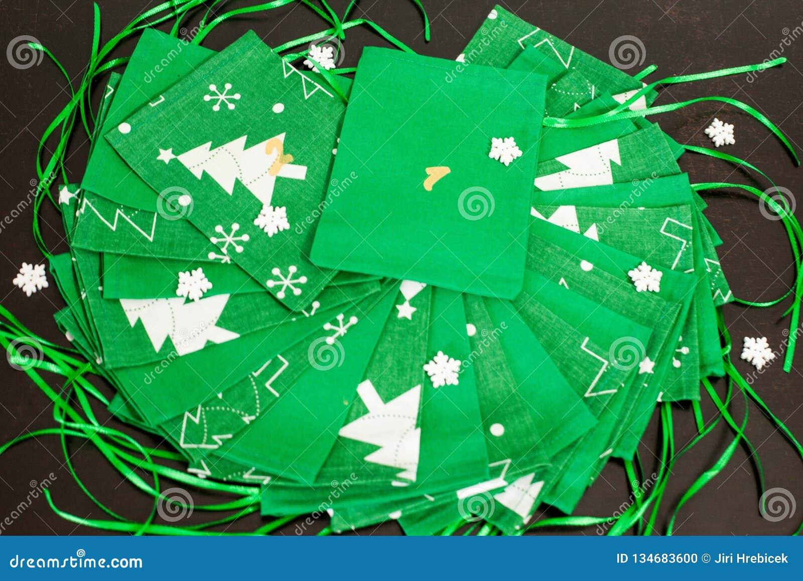 Den handgjorda juladventkalendern för barn, den röda adventen numrerade säckar som var klara att fyllas upp med leksaker