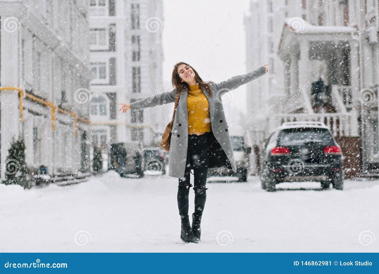 Den hellånga ståenden av den romantiska europeiska damen bär det långa laget i snöig dag Utomhus- foto av den inspirerade brunett