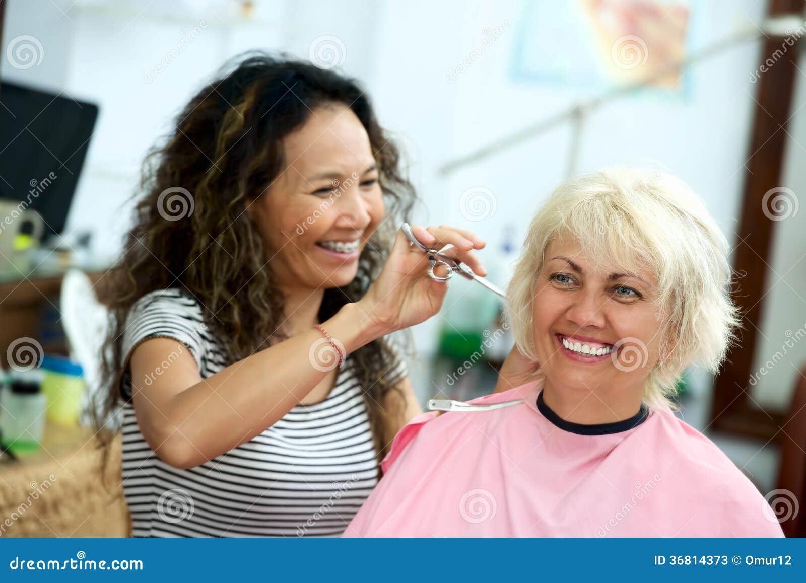 Den hem- asiatiska frisören klipper hår