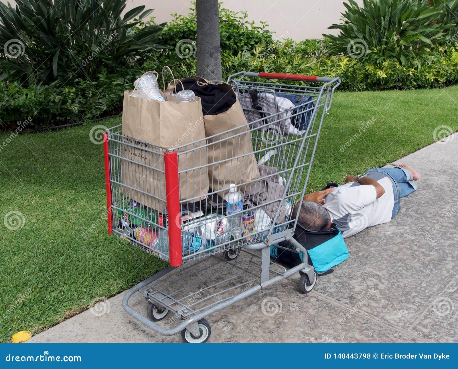 Den hemlösa mannen sover med huvudet som vilar på en påse på trottoaren