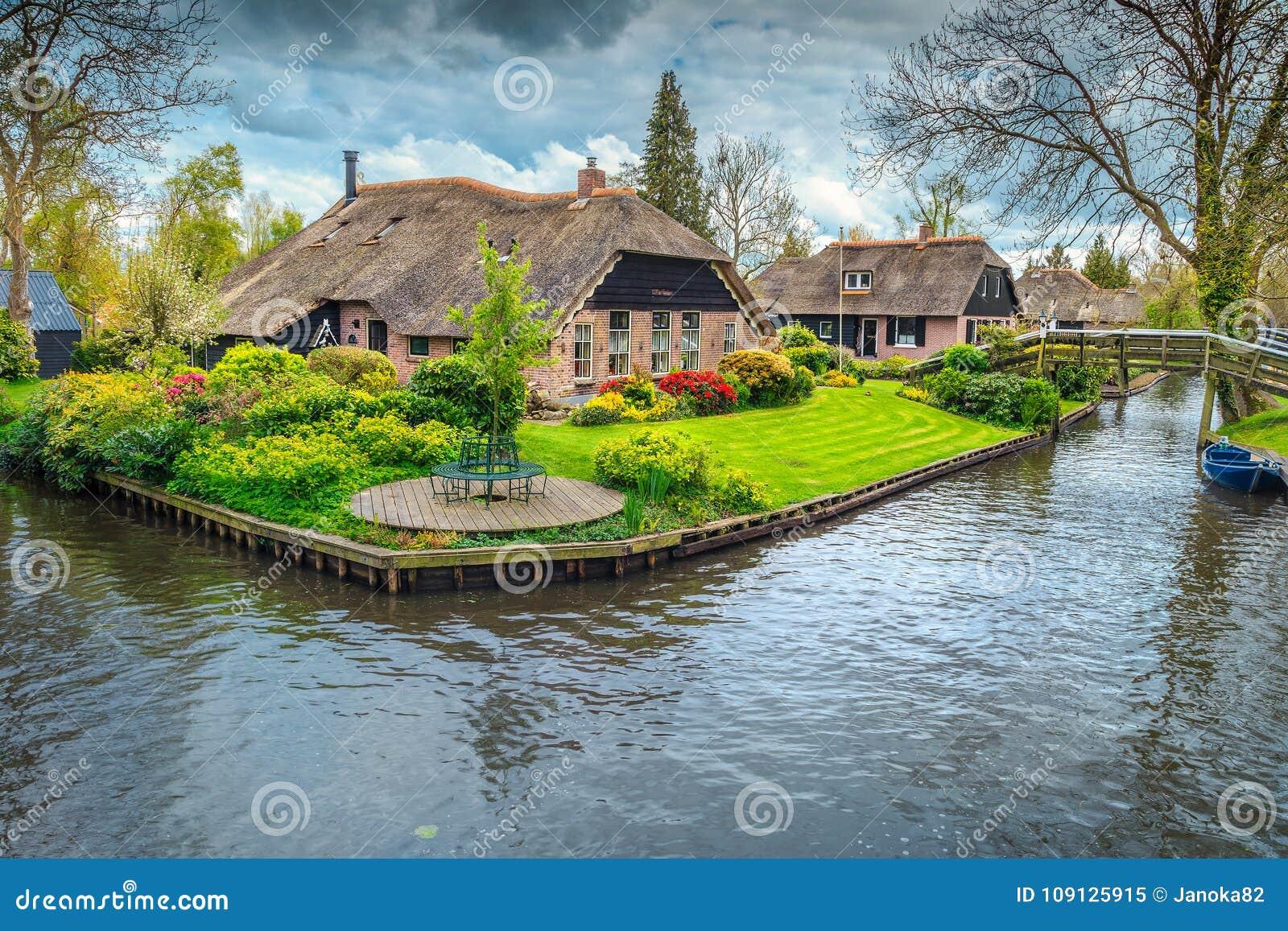 Den holländska byn med den färgrika dekorativa trädgården och våren blommar, Giethoorn