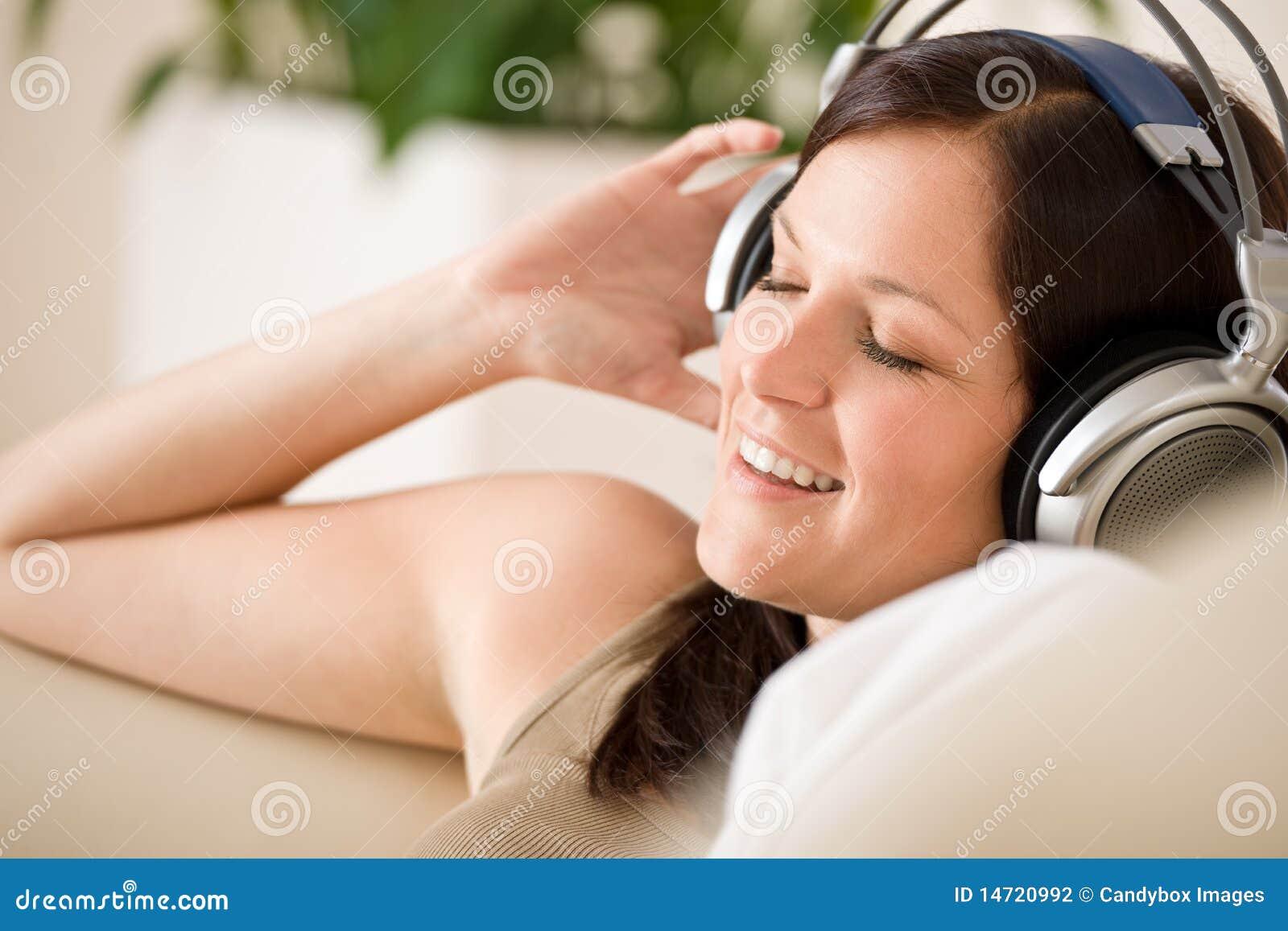 Den home hörlurar lyssnar musik som ler till kvinnan