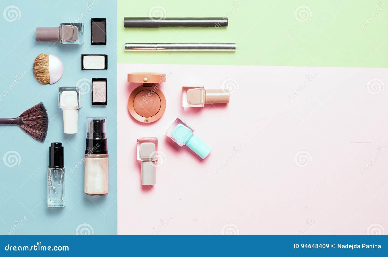 Den idérika lägenheten som är lekmanna- av ljust mode, spikar polermedel och den dekorativa skönhetsmedlet på en färgrik bakgrund