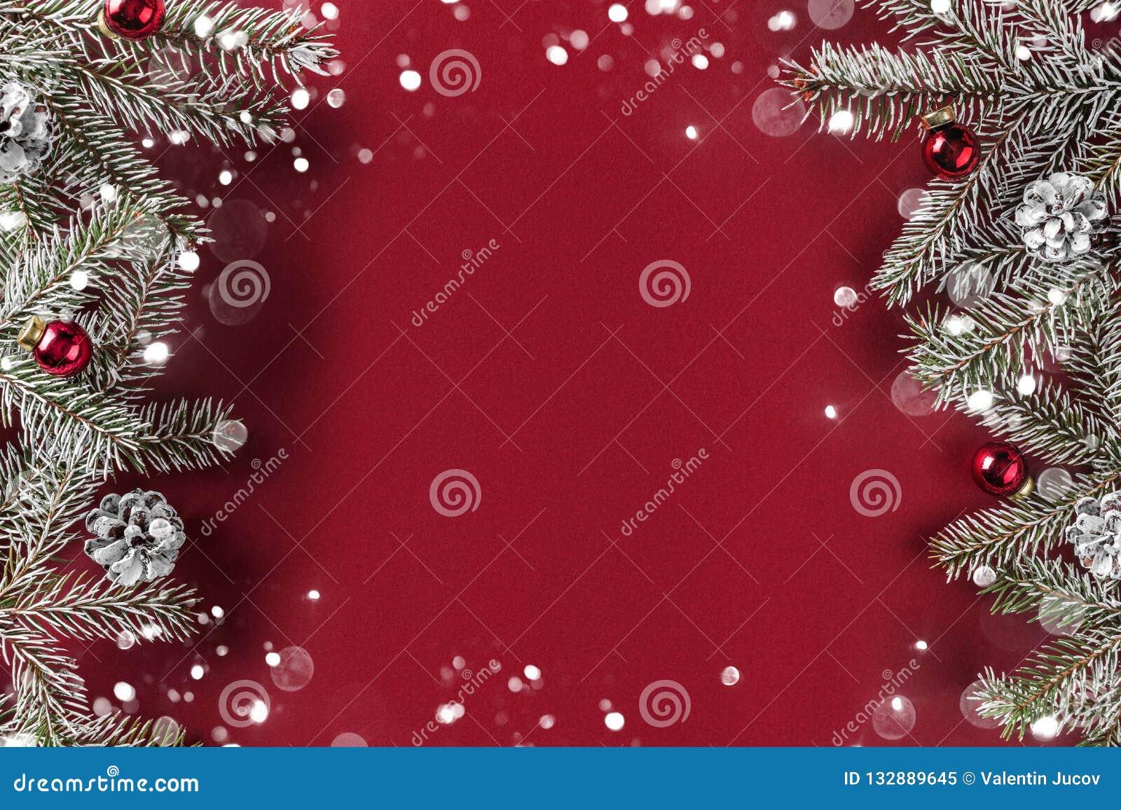 Den idérika orienteringsramen som göras av julgranfilialer, sörjer kottar, gåvor, röd garnering på röd bakgrund