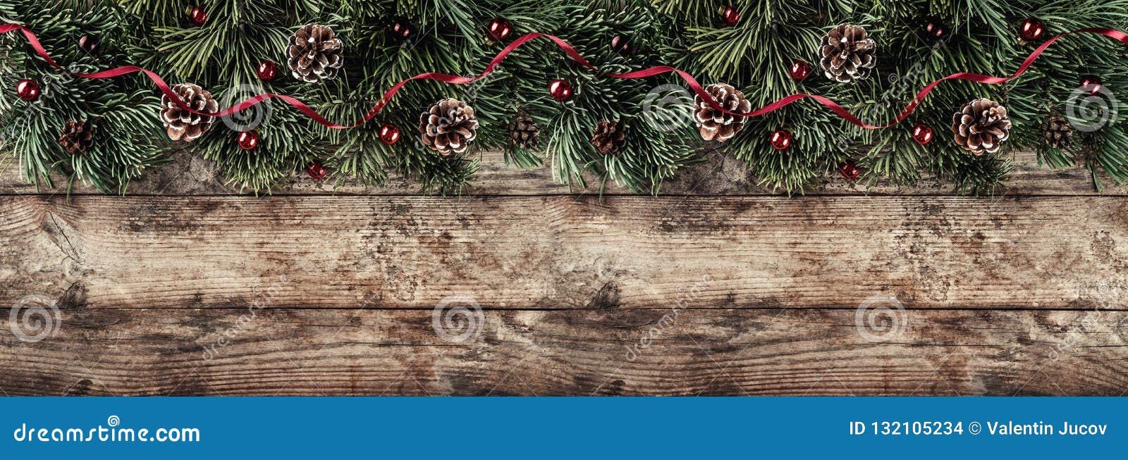 Den idérika orienteringsramen som göras av julgranfilialer, sörjer kottar och röd garnering på träbakgrund Tema för Xmas och för