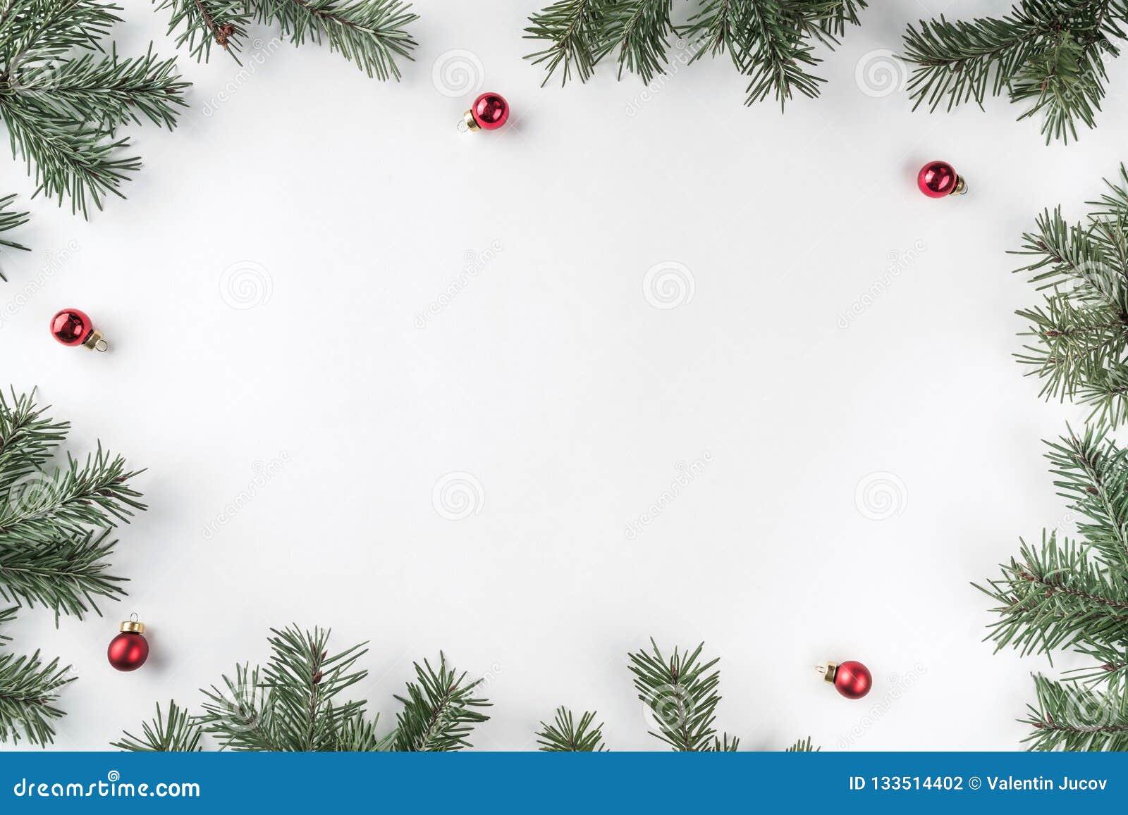 Den idérika ramen som göras av julgranfilialer på vit bakgrund med röd garnering, sörjer kottar