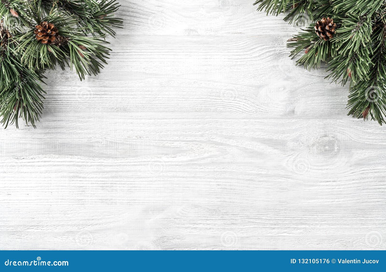 Den idérika ramen som göras av julgranfilialer på vit träbakgrund med, sörjer kottar Tema för Xmas och för nytt år