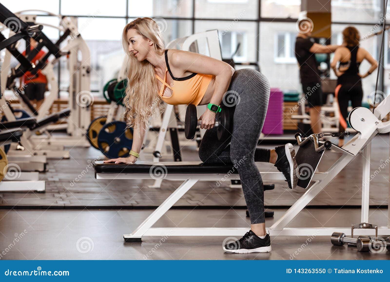 Den idrotts- blonda flickan med iklätt långt hår en sportswear gör övning på bänken med hantlar för triceps in