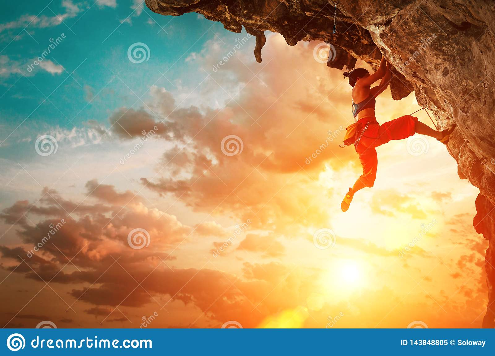 Den idrotts- kvinnan som klättrar på den hängande över klippan, vaggar med solnedgånghimmelbakgrund