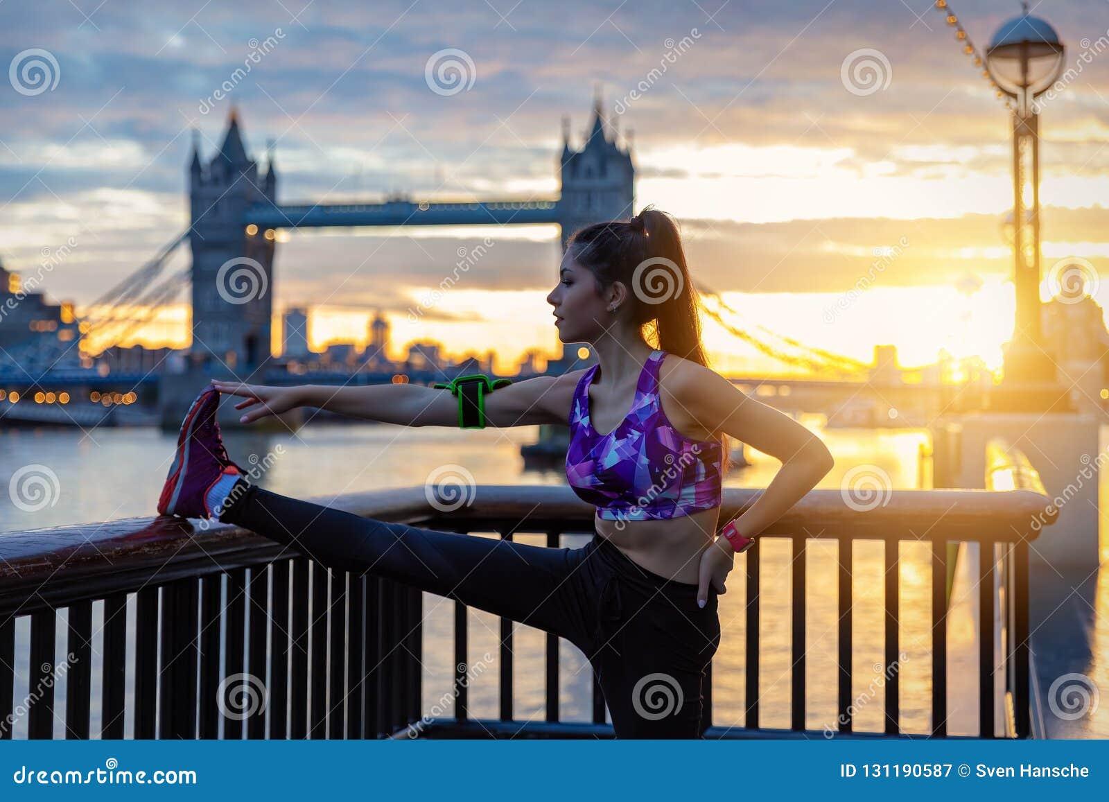 Den idrotts- stadskvinnan gör hennes elasticiteter framme av tornbron i London