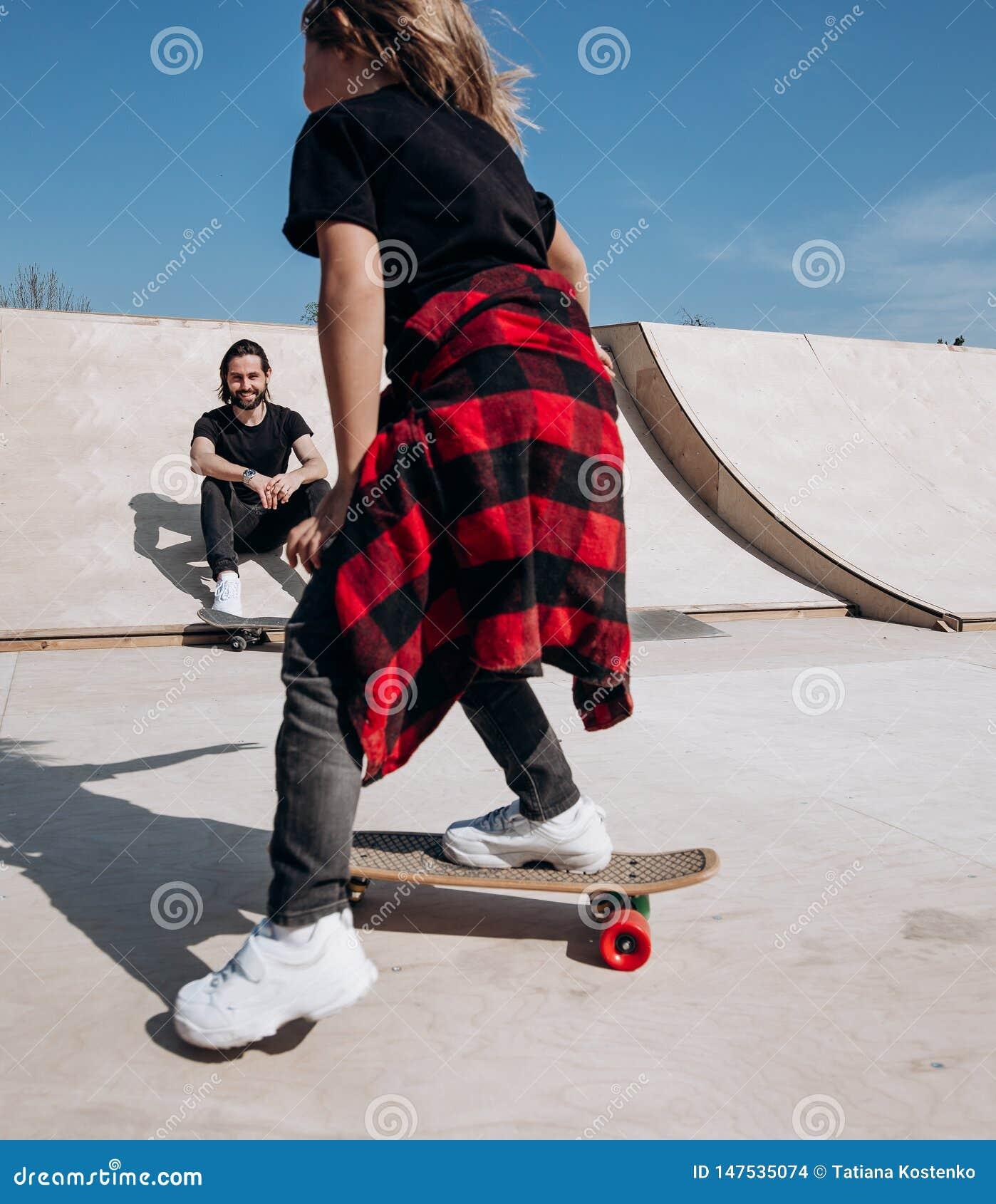 Den iklädda fadern och hans lilla son den tillfälliga kläderna rider skateboarder och har gyckel i en skridsko parkerar med glidb
