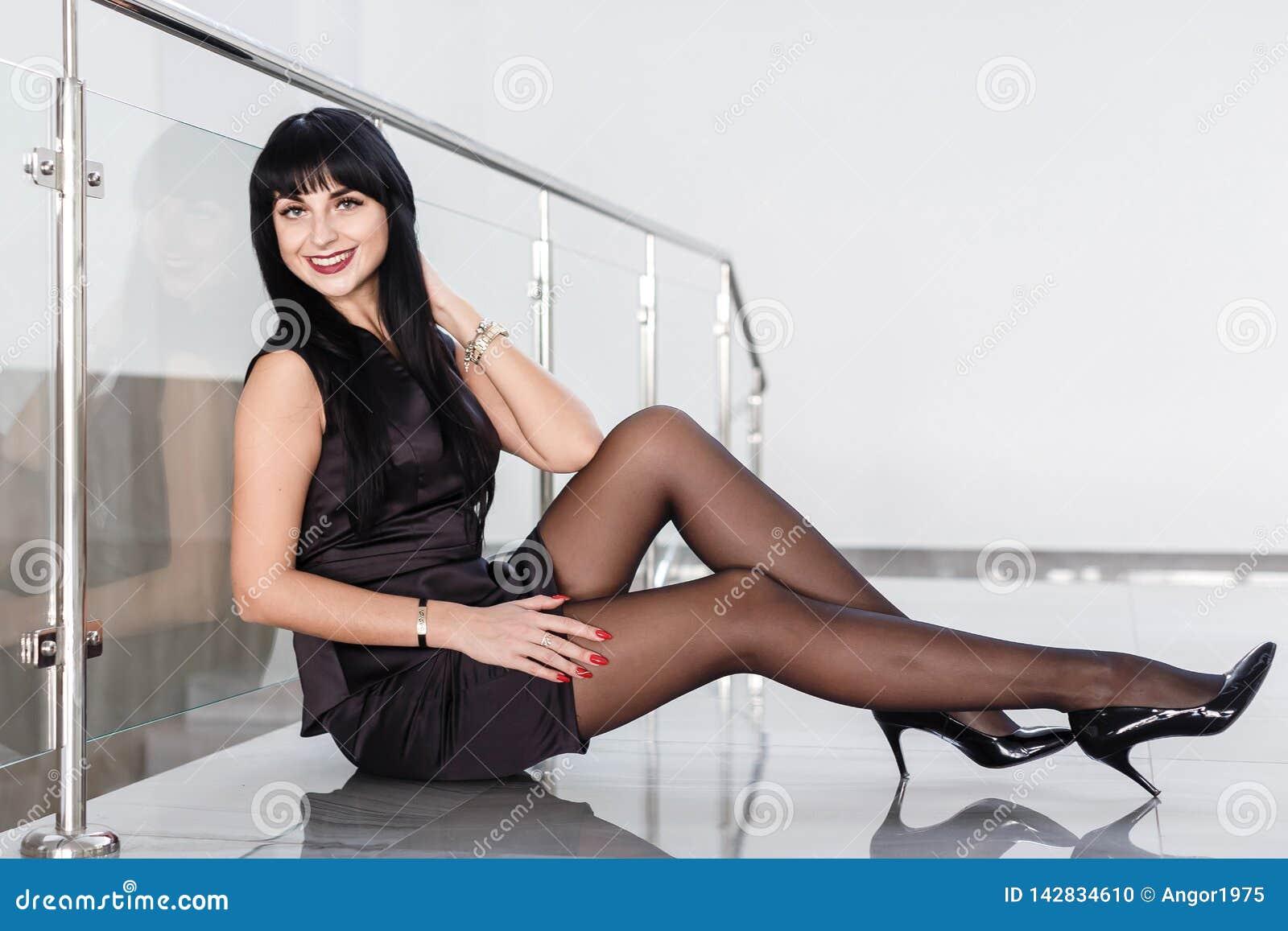 Den iklädda härliga unga kvinnan en svart affärsdräkt med en kort kjol sitter på ett golv i ett vitt kontor Att le,