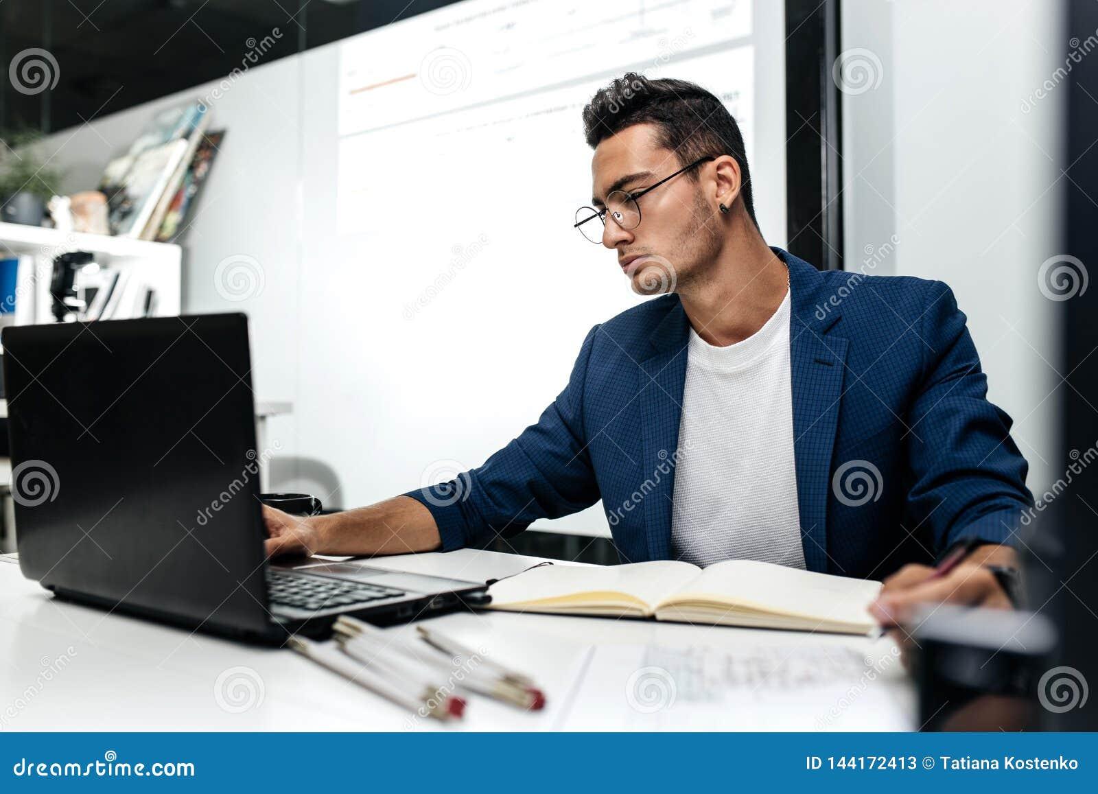Den iklädda Mörker-haired unga arkitekten ett blått omslag arbetar på bärbara datorn i kontoret