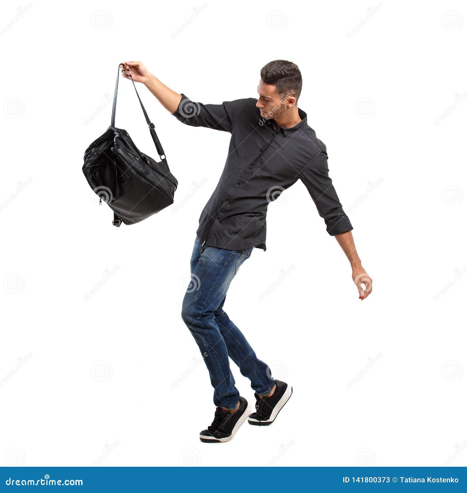 Den iklädda unga stilfulla mannen en svart skjorta och jeans poserar med den svarta ryggsäcken på den vita bakgrunden
