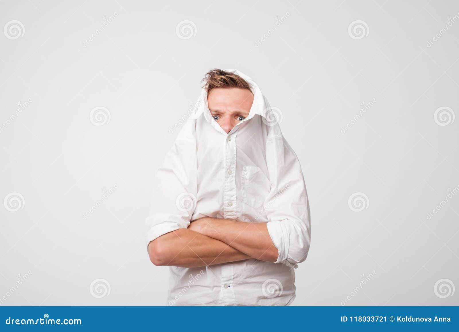 Den ilskna caucasian mannen drar en vit skjorta över hans huvud ensamhet av den deprimerade personen