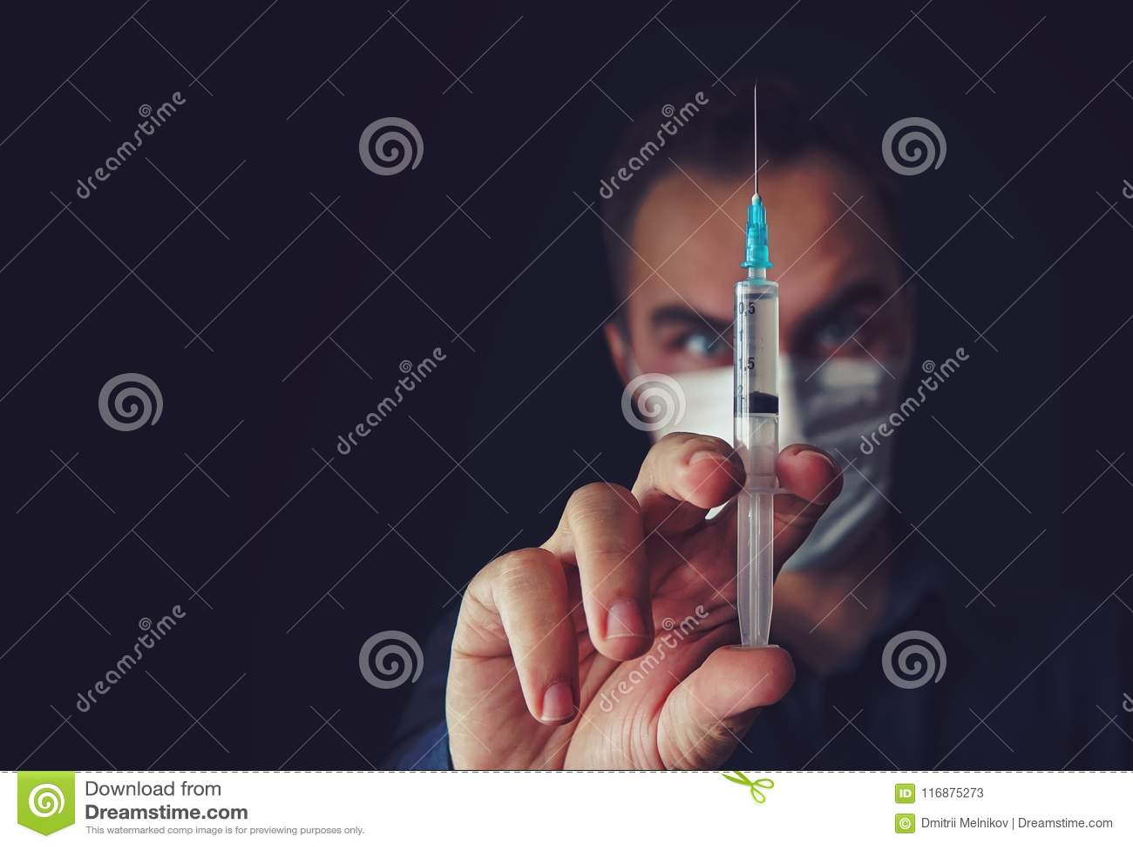 Den ilskna doktorskvinnan i en medicinsk maskering rymmer en injektionsspruta