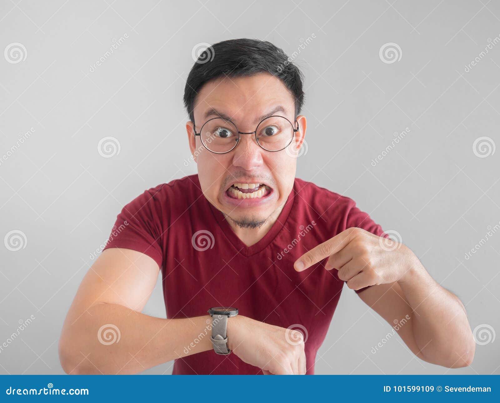 Den ilskna och otrevliga framsidan av mannen ser hans vänta för klocka