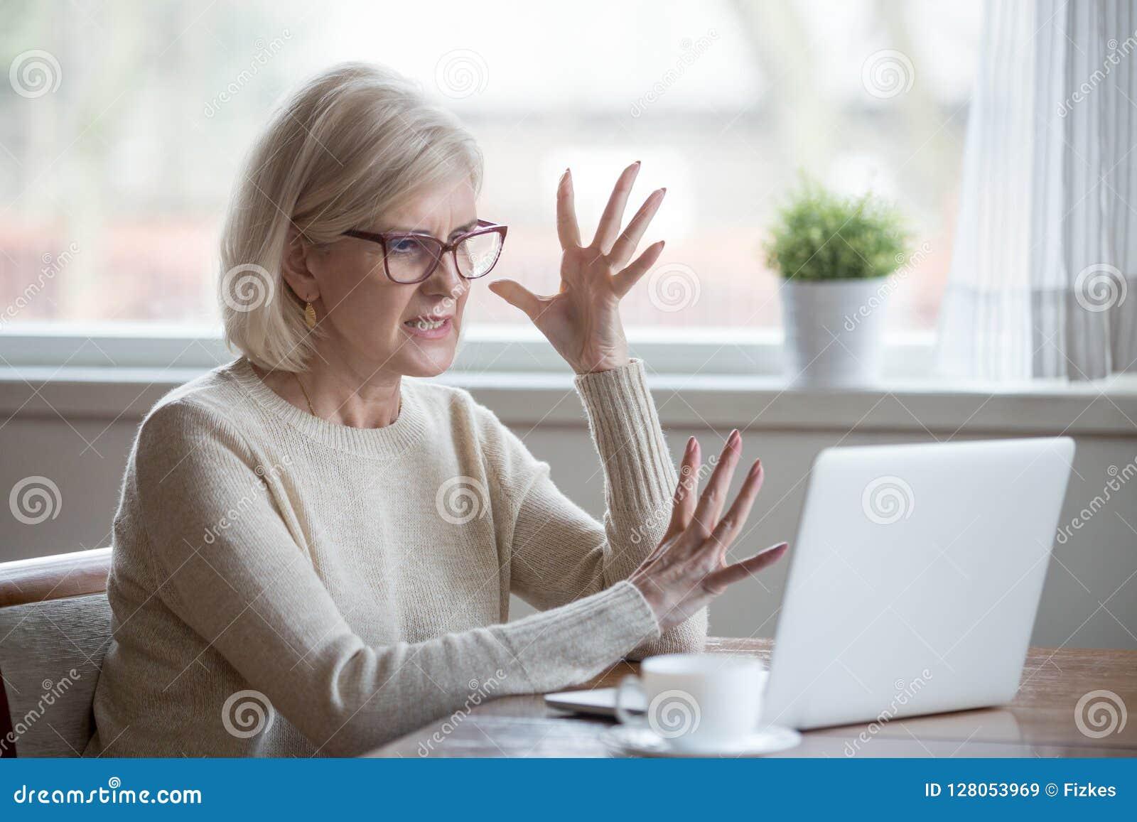 Den ilskna stressade mitt åldrades affärskvinnan som förargades med datoren