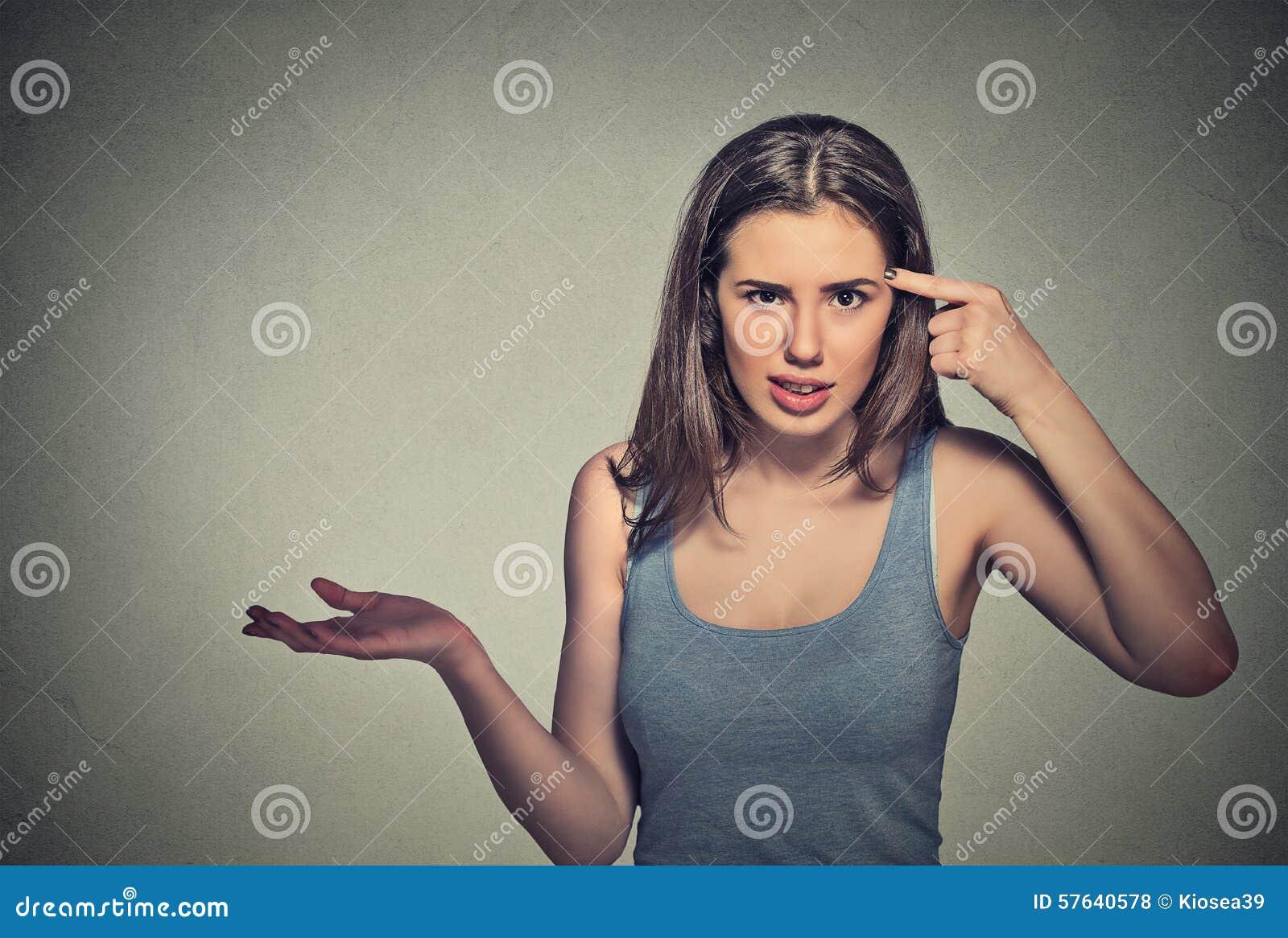 Den ilskna unga kvinnan som gör en gest att fråga, är dig som är galen?