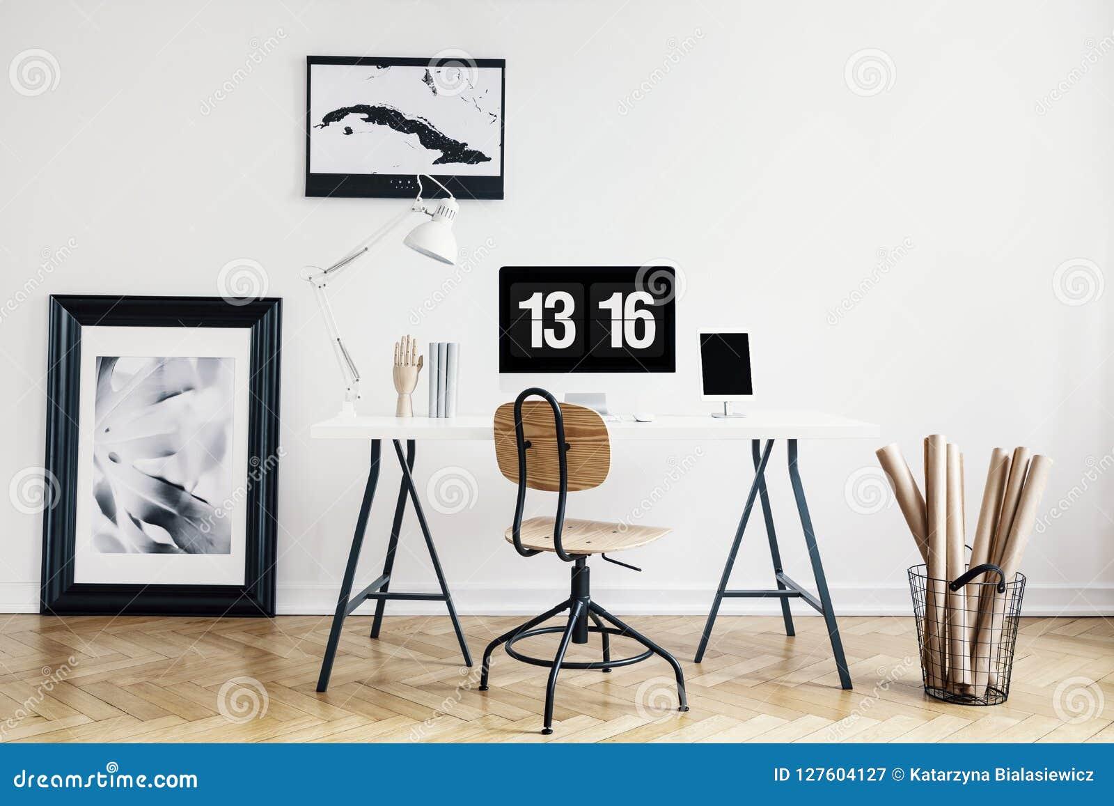 Den industriella korgen med kraft papper rullar och en inramad affisch i en vit, minimalist inrikesdepartementetinre av en freela