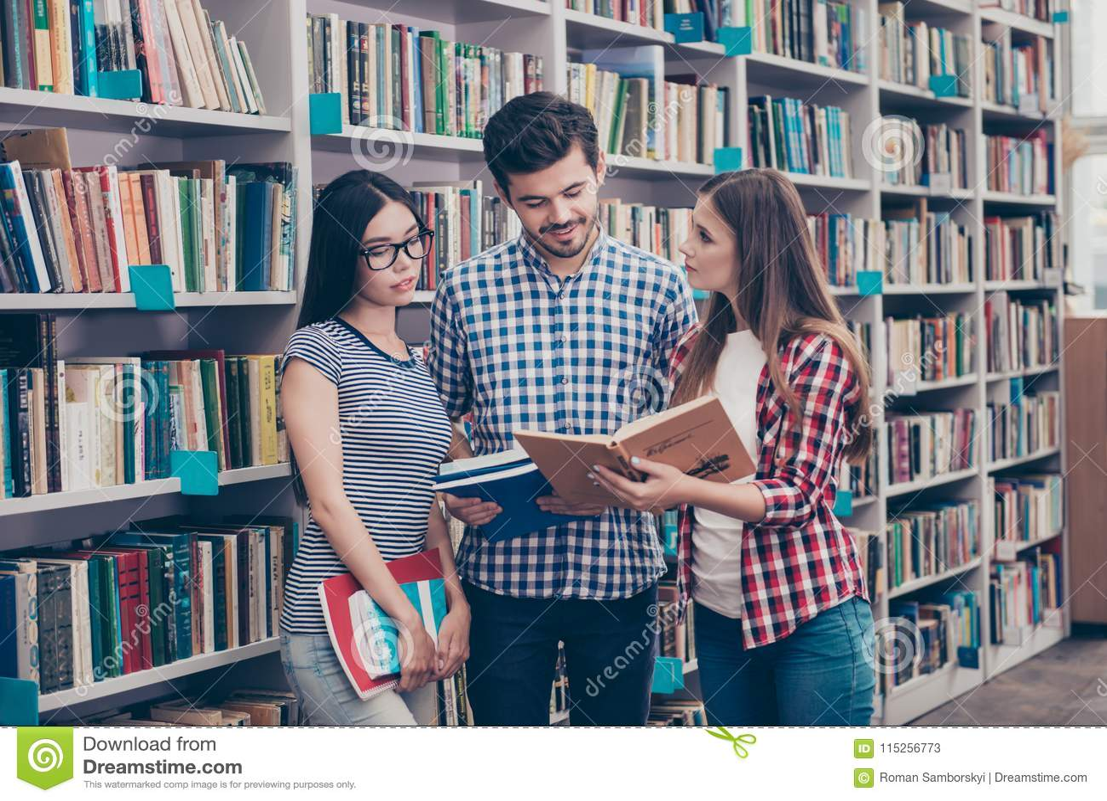 Den internationella gruppen av tre fokuserade klyftig ung studentbookw