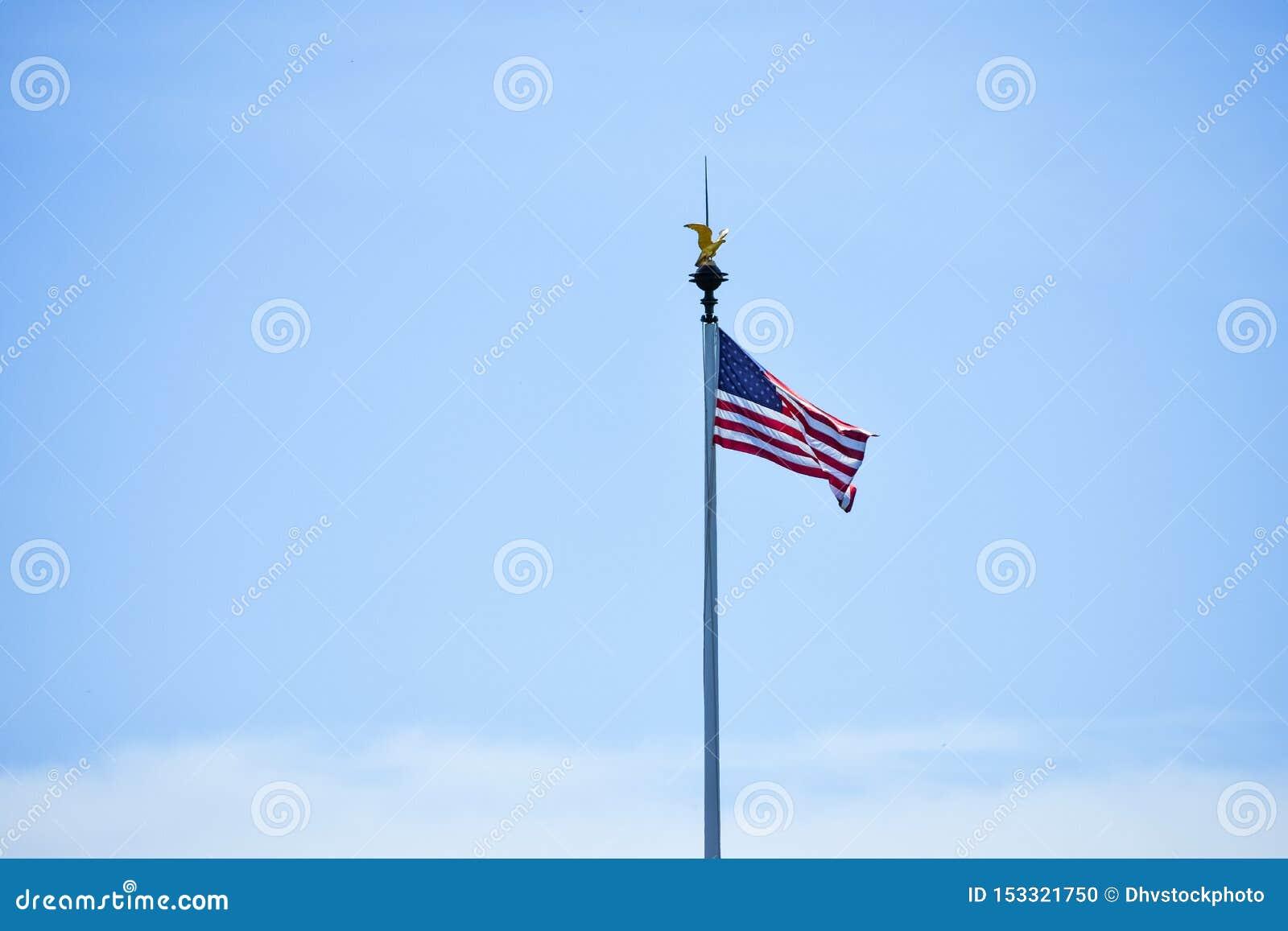 Den isolerade Förenta staterna sjunker att vinka i vinden i en bakgrund för blå himmel Kopiera utrymme f?r text
