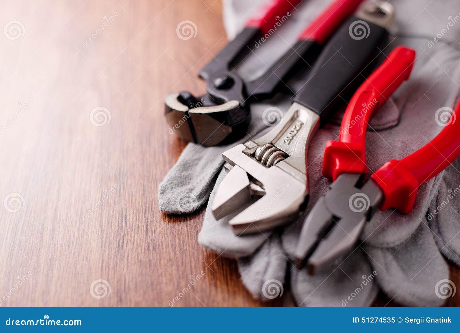 Den justerbara skiftnyckeln, plattång och spikar pulleren överst av de skyddande handskarna