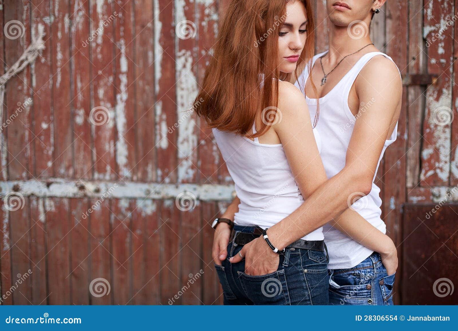 Den känslobetonade ståenden av ett stilfullt kopplar ihop i jeans som tillsammans står