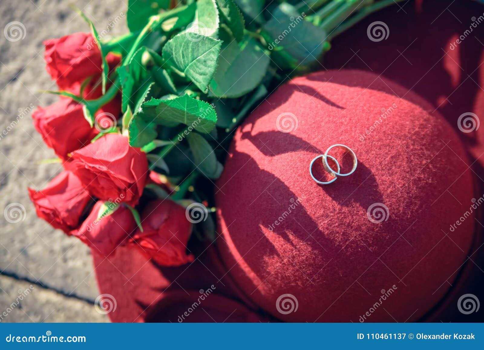 Den körsbärsröda hatten med den rosa buketten och vigselringar på stenen ytbehandlar