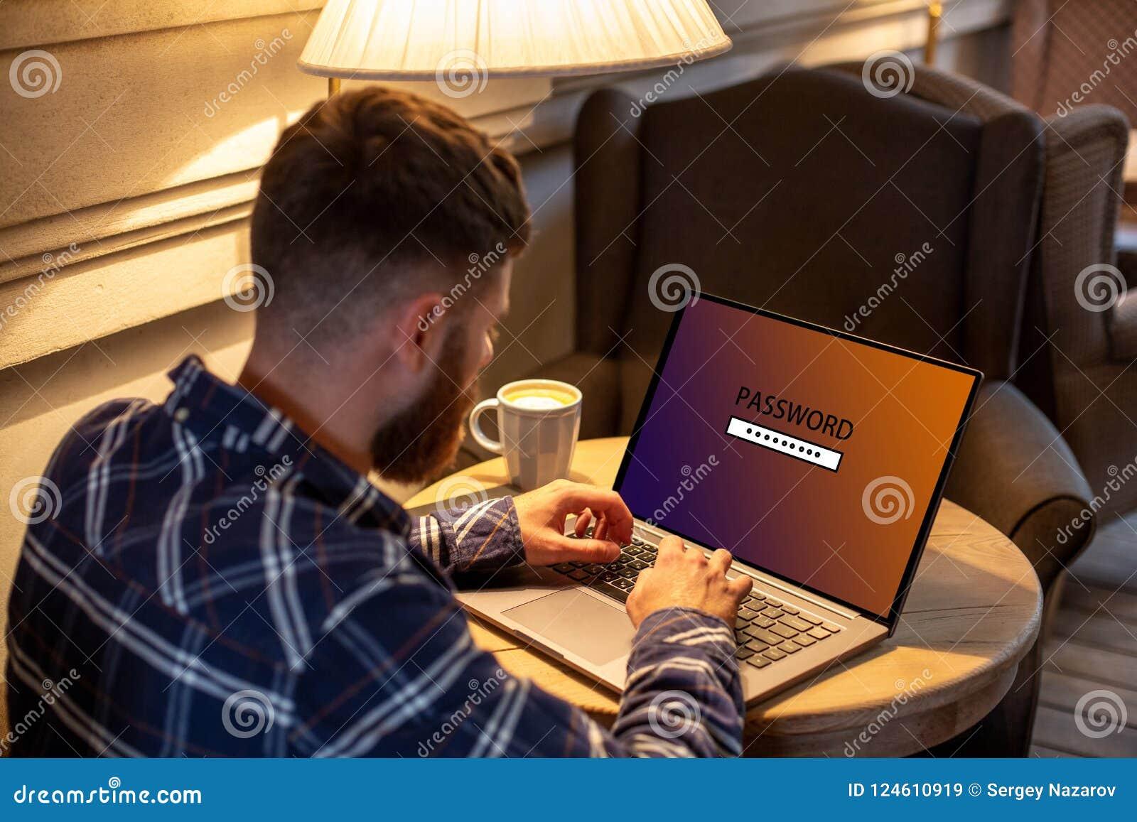 Den kantjusterade bilden av en ung man som arbetar på hans bärbar dator i en coffee shop, den unga manliga studenten, skriver in