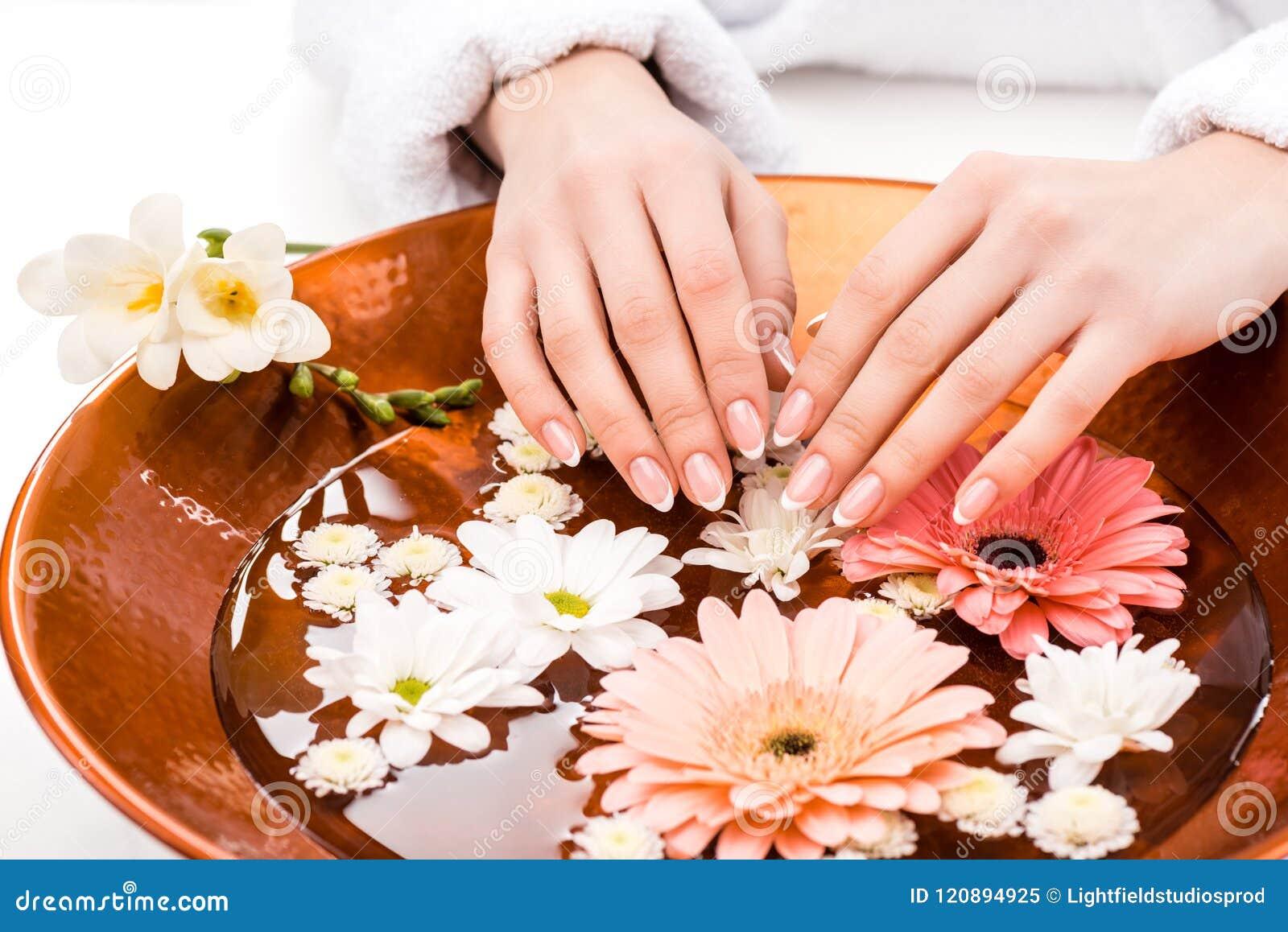 Den kantjusterade sikten av tillvägagångssättet för kvinnadanandebrunnsorten med blommor i skönhetsalong, spikar