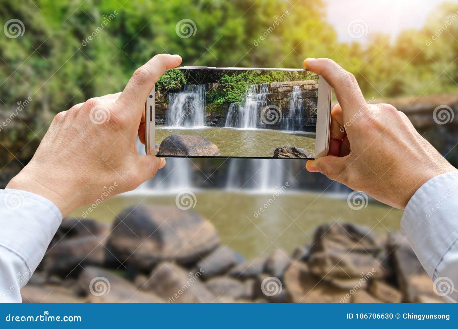 Den kantjusterade skottsikten av man` s räcker danandefotoet på mobiltelefonen