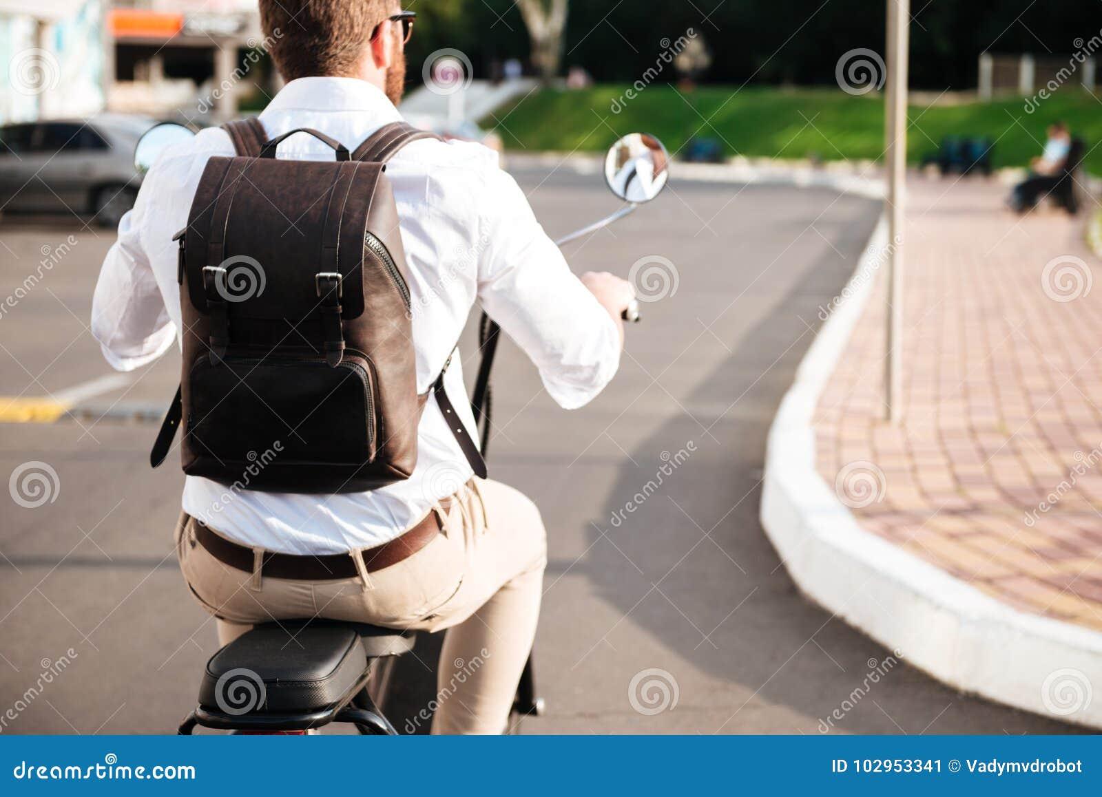 Den kantjusterade tillbaka sikten av mannen med ryggsäcken rider på mopeden