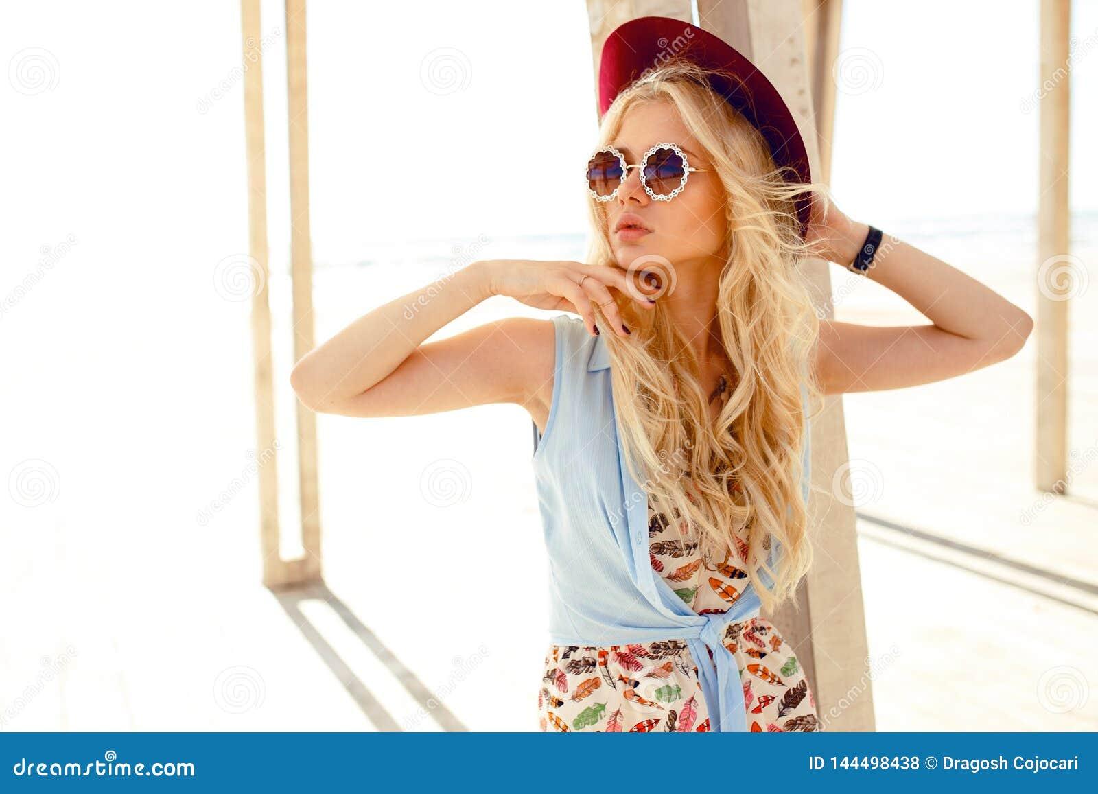 Den karismatiska blonda flickan med rund solglasögon och hatten tycker om solen på havet Horisontalsikt på den ljusa bakgrunden