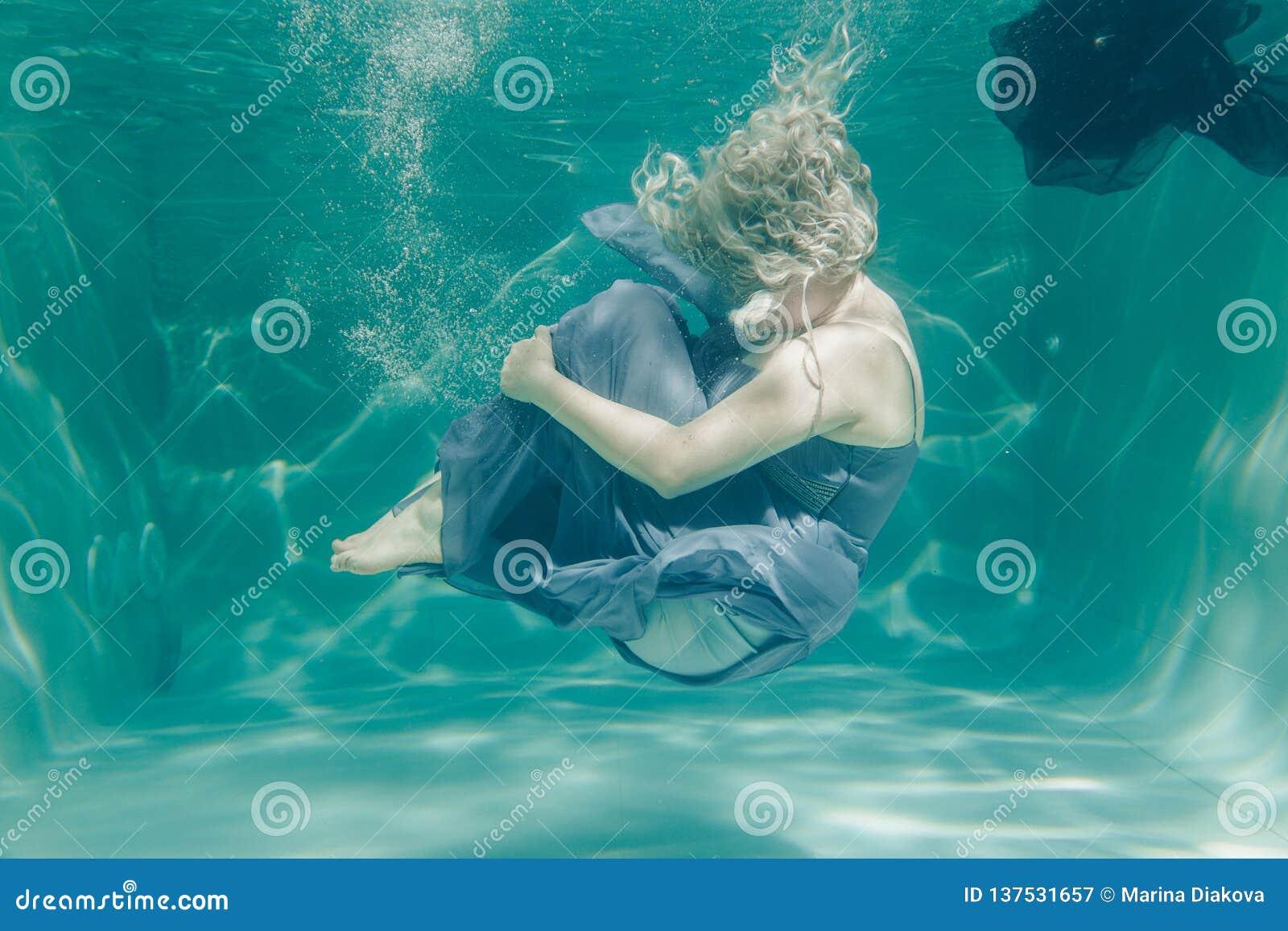 Den knubbiga kvinnan i simma för klänning för grå afton som långt är undervattens- på hennes ferier och, tycker om med kopplar av