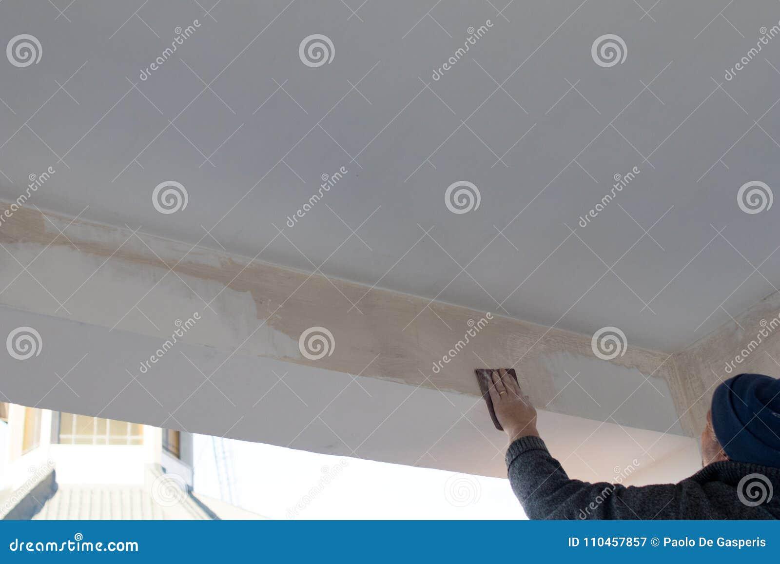 Den kompetenta arbetaren fördelar stuckaturen och målarfärg på en stråle av en terrass D