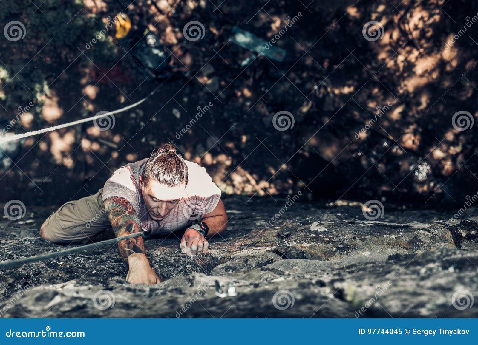 Den koncentrerade manliga klättraren klättrar ett brant vaggar Extremt begrepp för utomhus- aktivitet för livsstil